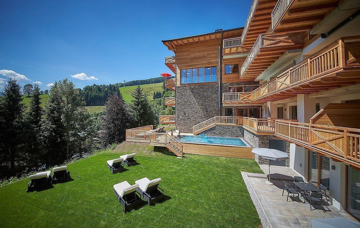Sommerliche Außenansicht inklusive Pool und Liegewiese