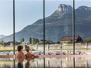 Verliebtes Paar genießt im Pool den Ausblick auf die Berge im Ausseerland