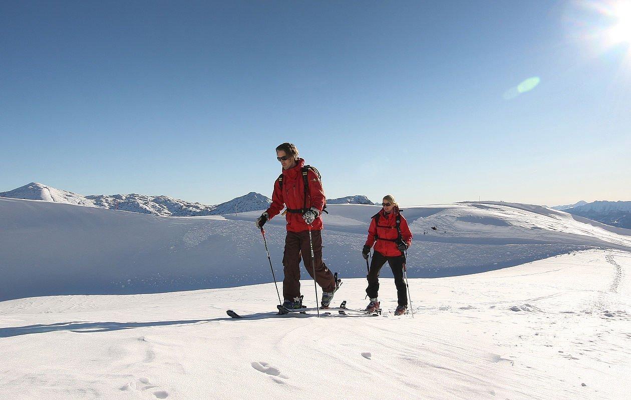 Zwei Skitourengeher marschieren durch die verschneite Landschaft im Salzkammergut