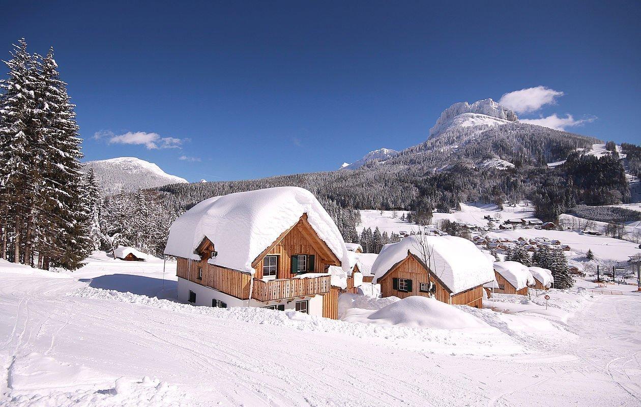 Ferienhäuser mit dicker Schneedecke am Dach
