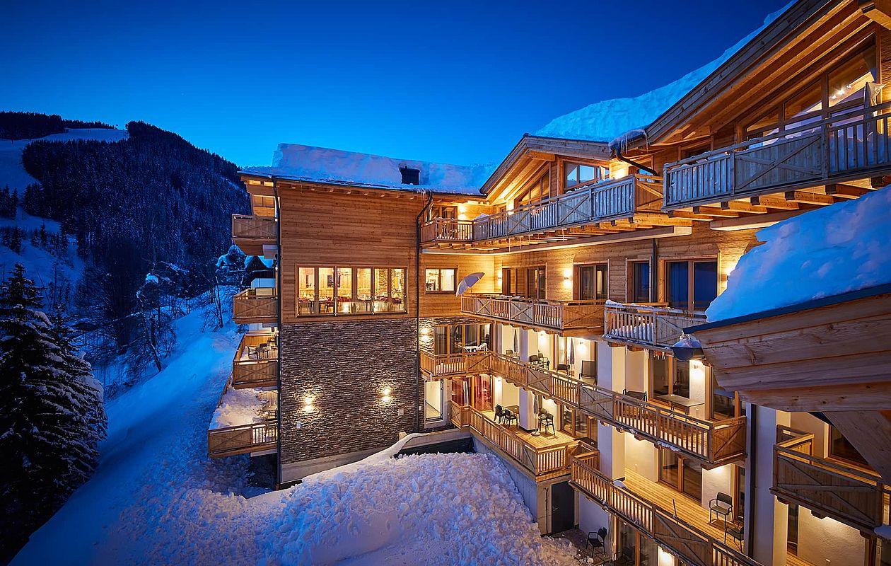 Hotelgebäude mit Beleuchtung bei Abenddämmerung in Saalbach
