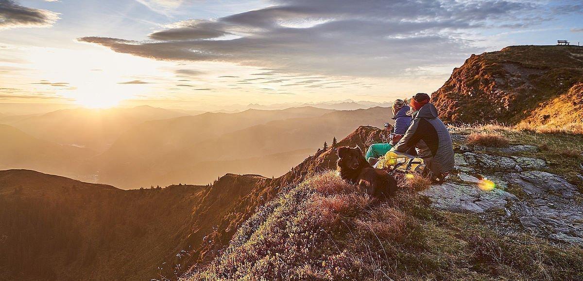 Pärchen mit Hund genießt Sonnenaufgang am Gipfel in Saalbach-Hinterglemm