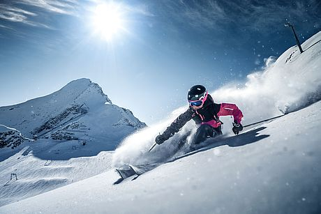 Skifahrer wedelt im Tiefschnee und bei Sonnenschein