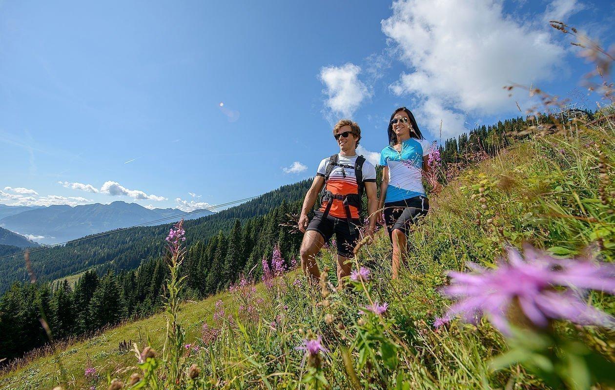 Junges Paar wandert durch eine Blumenwiese in den Bergen