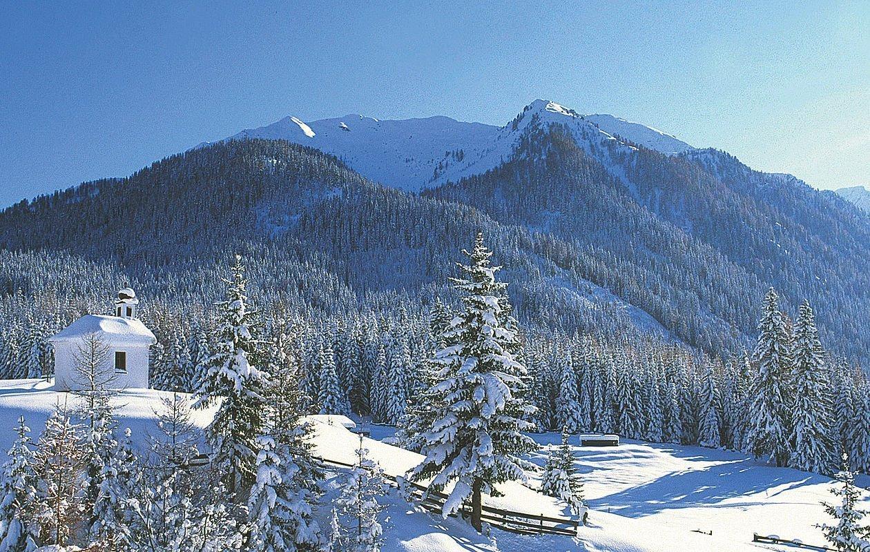 Tiefverschneite Winterlandschaft mit einer Kapelle