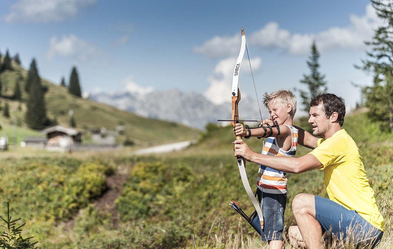 Vater und Sohn beim Bogenschießen in den Bergen