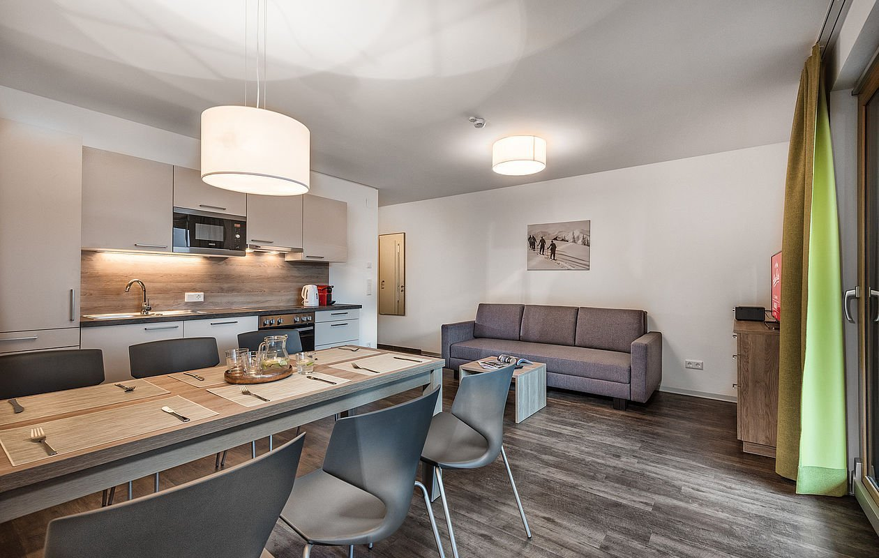 Wohnraum mit Einbauküche und großem Esstisch