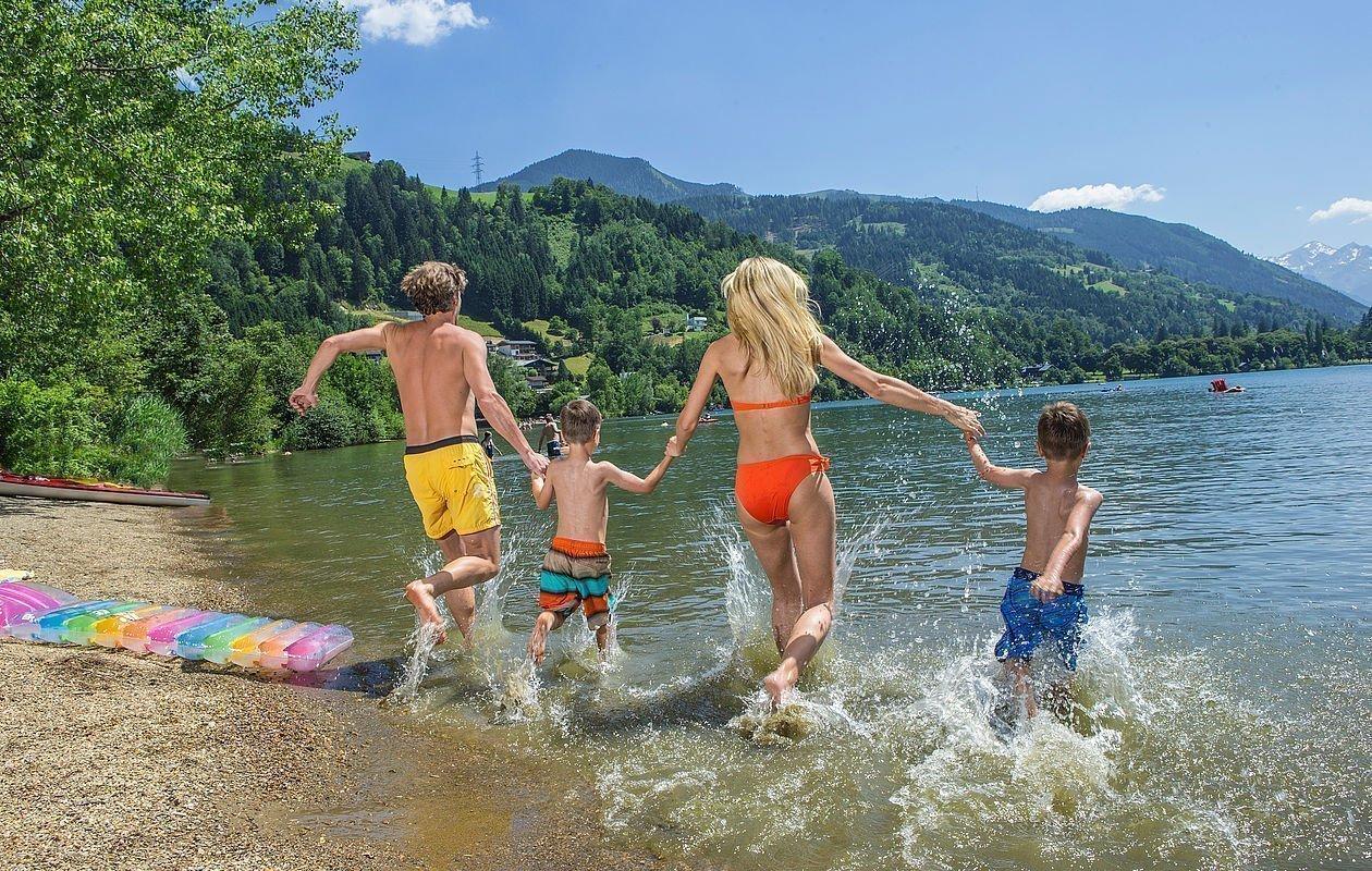 Junge Familie springt lachend in den Zeller See