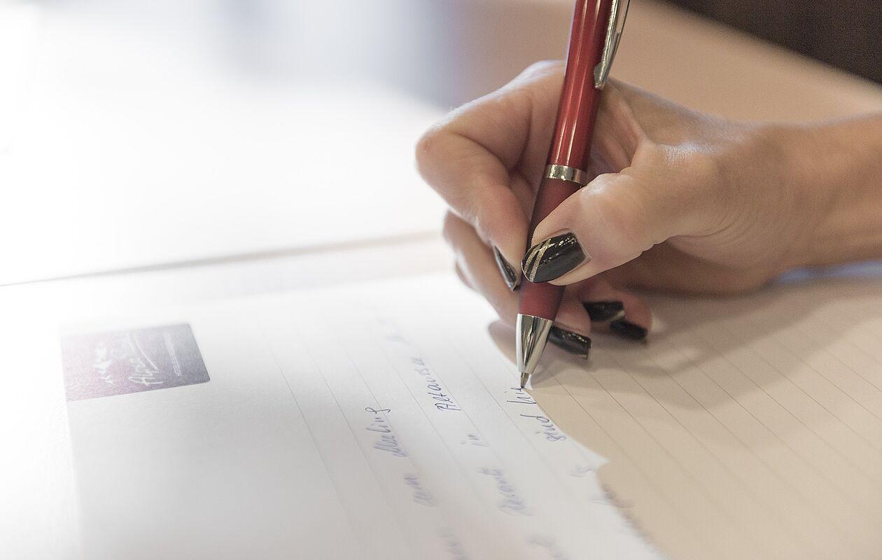Frau schreibt sich beim Seminar Notizen auf