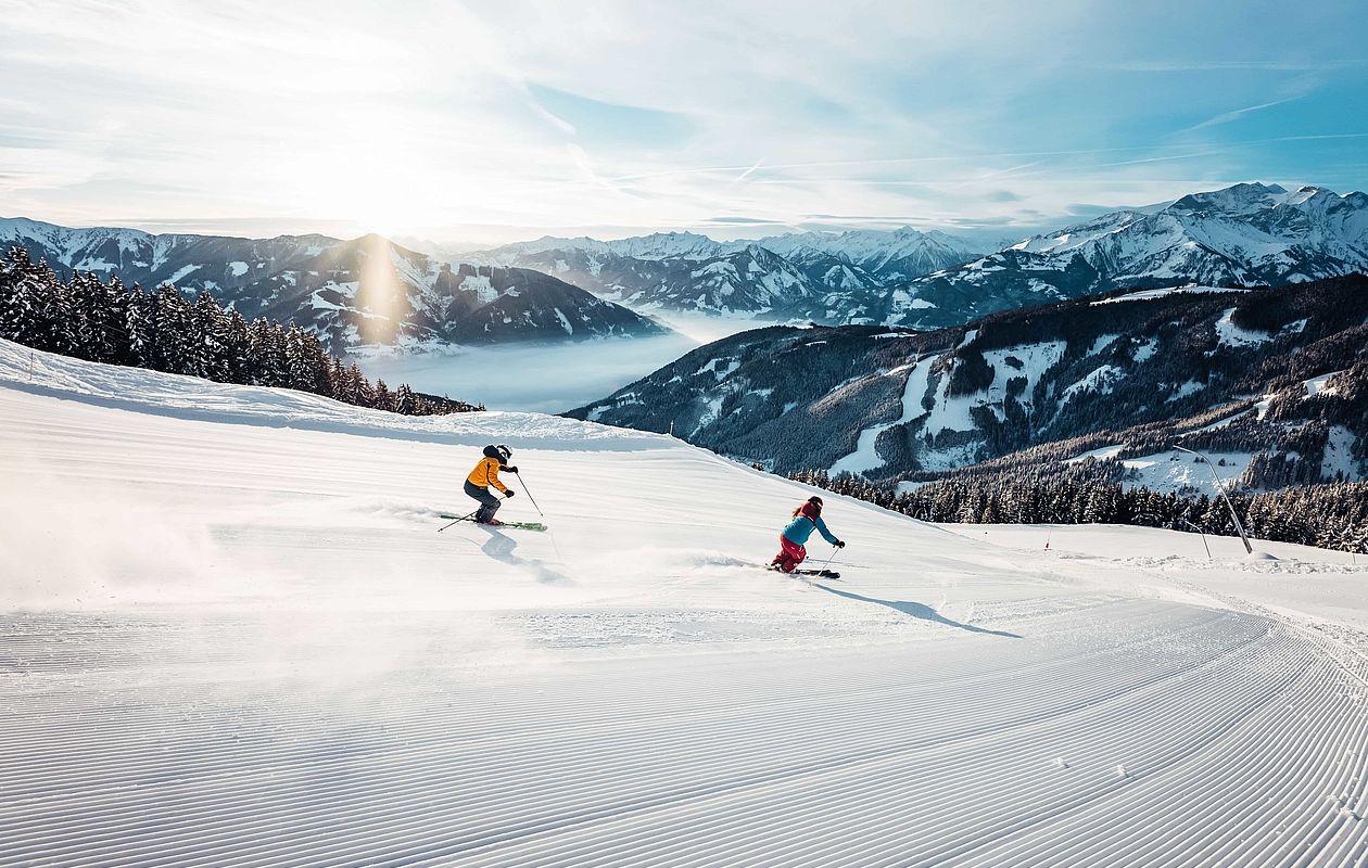 Zwei Skifahrer wedeln präparierte Piste am Morgen runter
