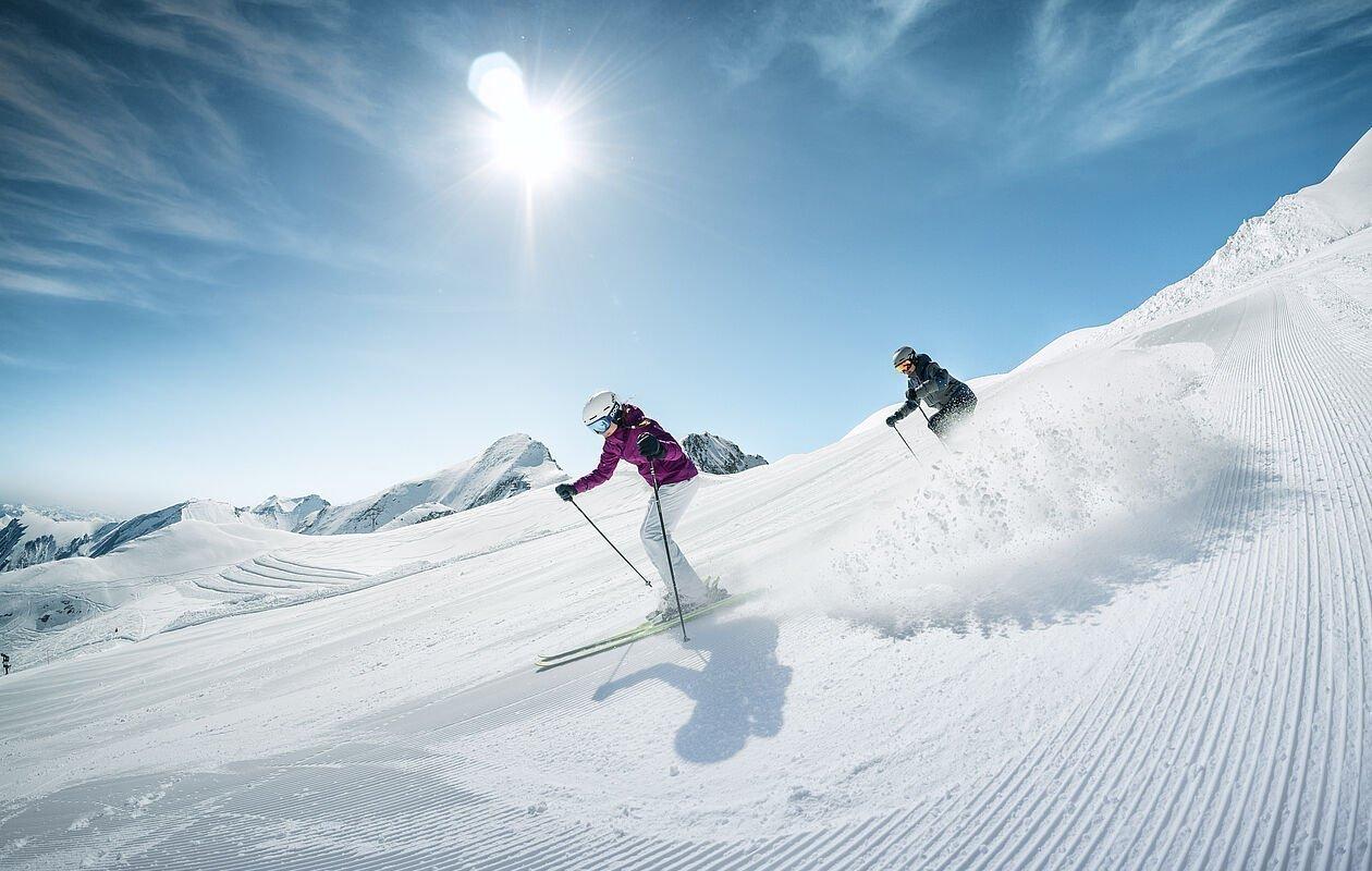 Zwei Skifahrer düsen bei Sonnenschein die Pisten runter