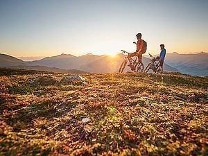 2 Mountainbiker stehen am Berg und genießen den Sonnenuntergang in Saalbach