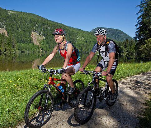 Mountainbiker mit Helm fahren bei Sonnenschein am Altausseer See entlang