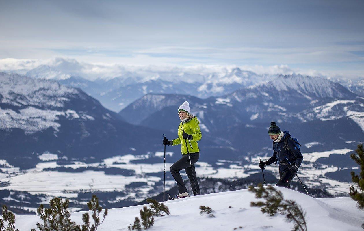 Paar wandert mit Schneeschuhen über einen Grat in den Bergen
