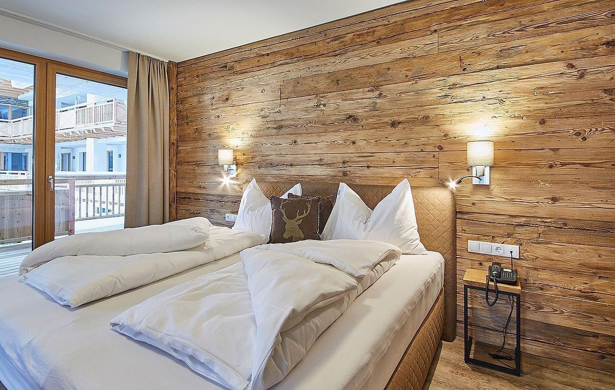 Modernes Schlafzimmer mit Doppelbett und Holzwand