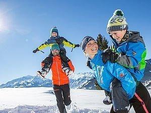 Eltern tragen Kinder im Schnee Huckepack