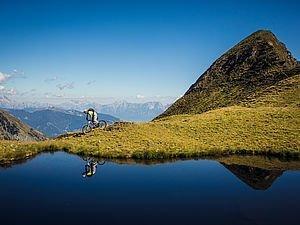 Mountainbiker fährt bei einem Bergsee in Kaprun vorbei