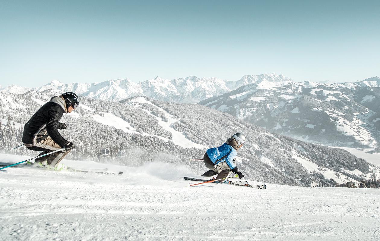 Skifahrer wedeln die Pisten von Zell am See runter