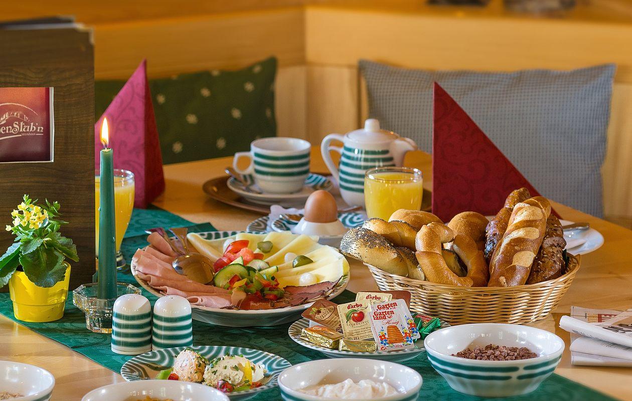 Reichlich gedeckter Frühstückstisch mit Brötchen, Kaffee, Käse & Wurst, Müsli, Eiern und vielem mehr