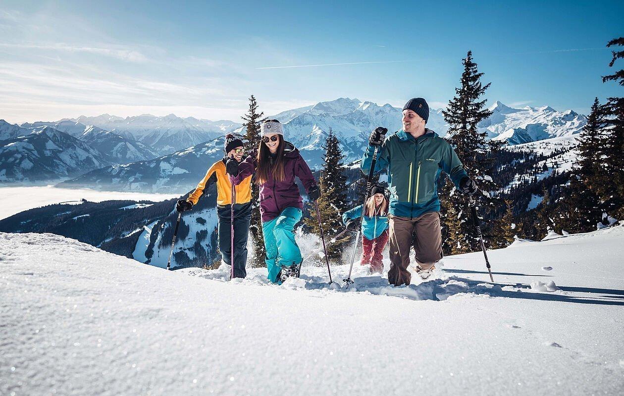 Junge Gruppe wandert mit Schneeschuhen durch die Winterlandschaft in Zell am See