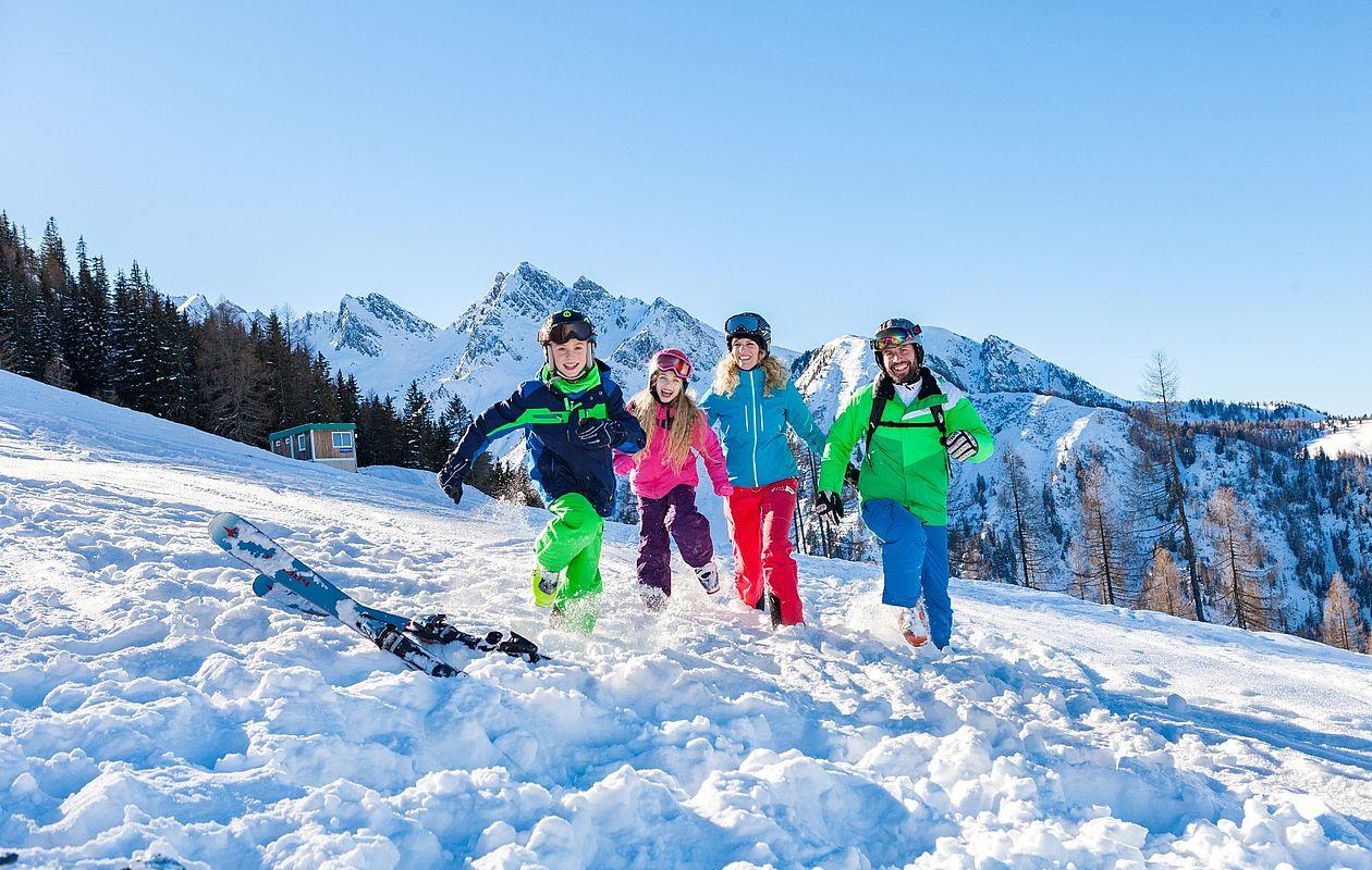 Junge Familie spielt im Schnee fangen