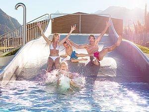 Familie mit Kindern genießt die Sonne auf den Rutschen der Tauern SPA Kaprun