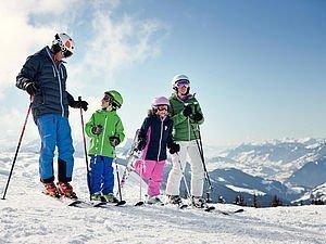 Familie genießt Aussicht über die Berge beim Skifahren