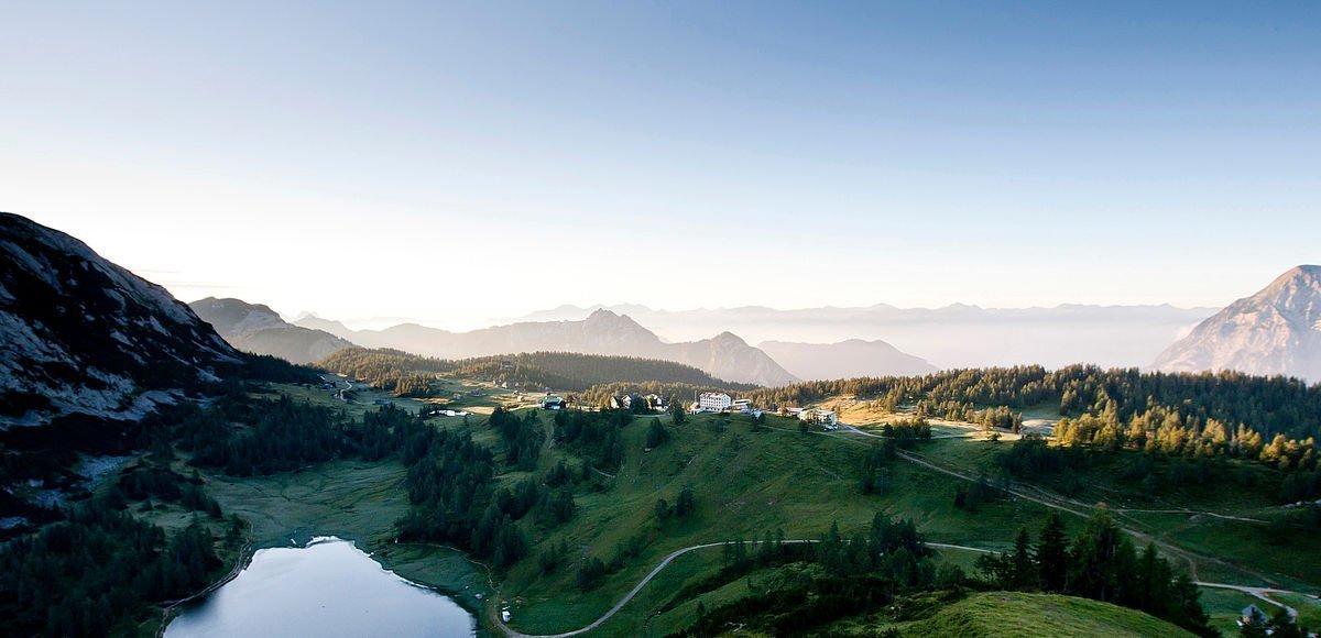 Glasklarer Bergsee bei Sonnenaufang mit mystischen Nebelfeldern