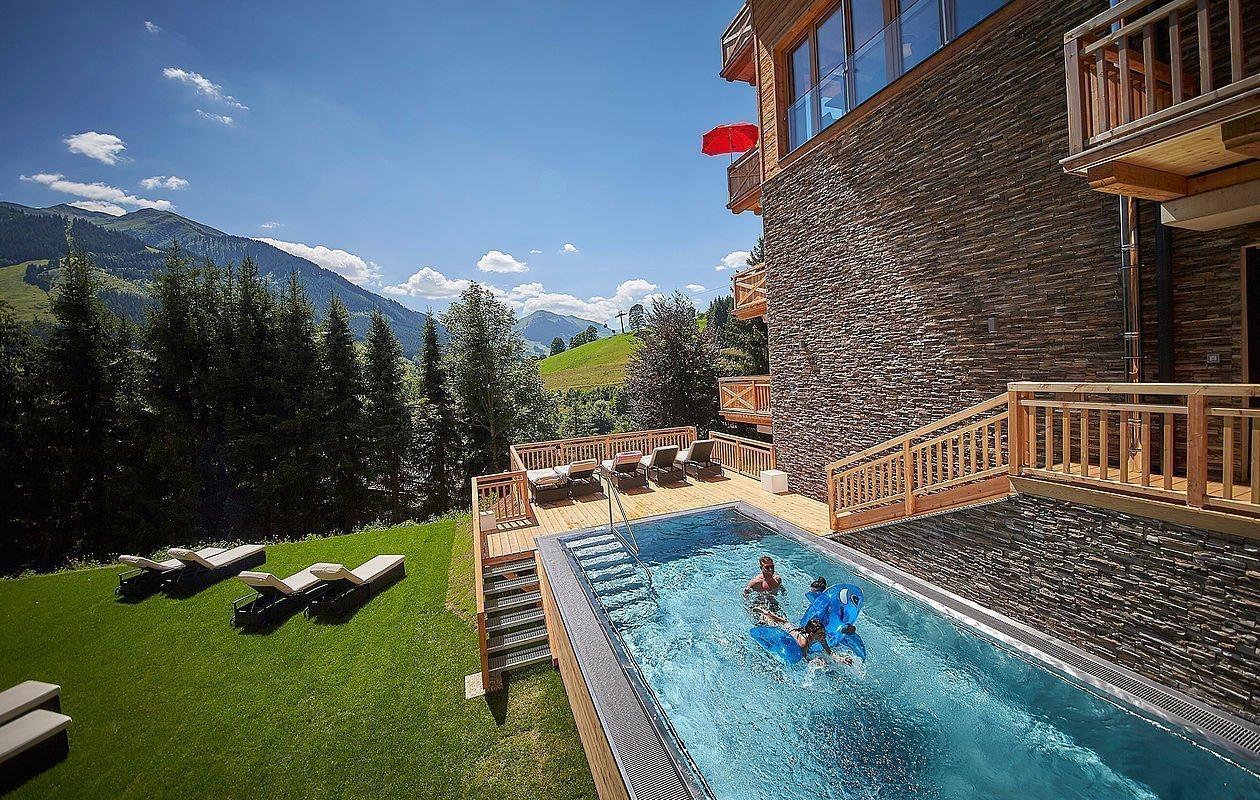 Hotel-Außenansicht mit Pool und Blick auf die Berge von Saalbach