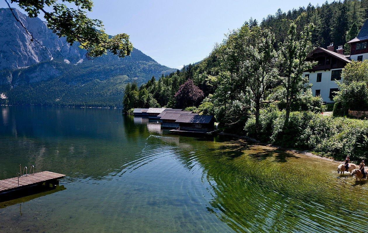 Glitzerndes grünes Wasser mit Steinen und einem Steg vor Bergpanorama