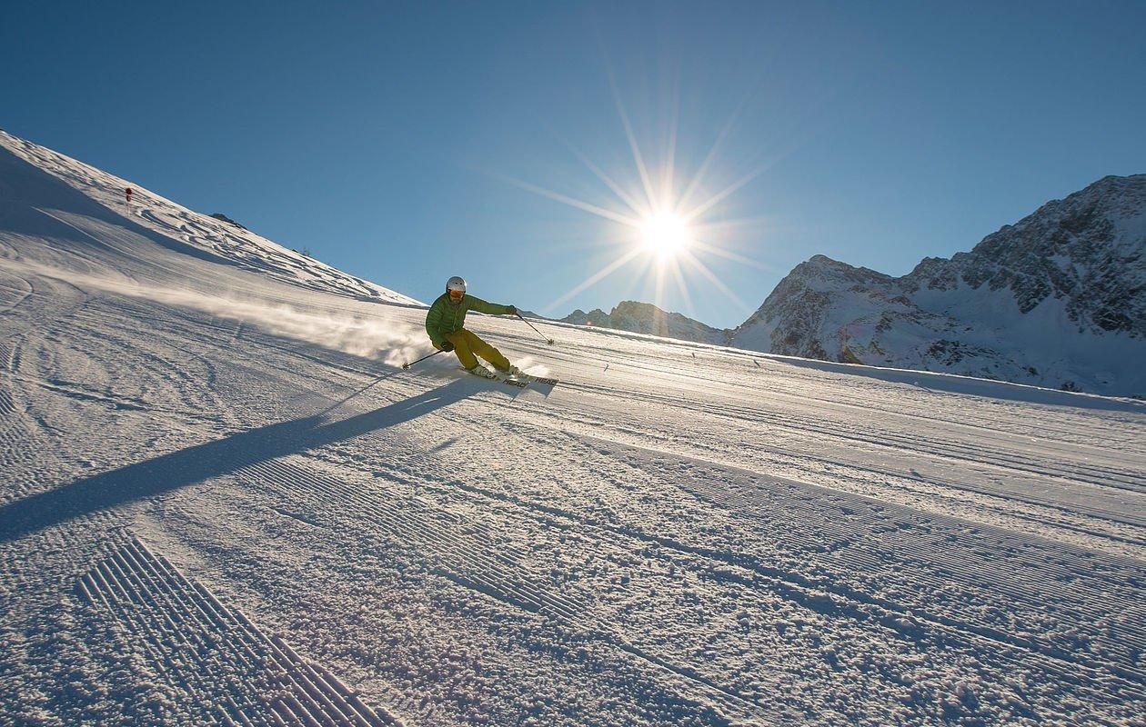 Skifahrer zieht seine Schwünge bei Sonnenaufgang