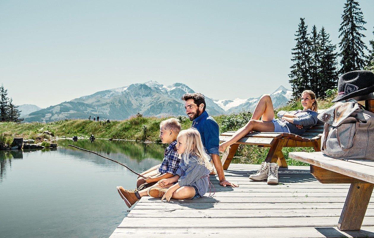 Familie picknickt am Speicherteich auf der Schmittenhöhe