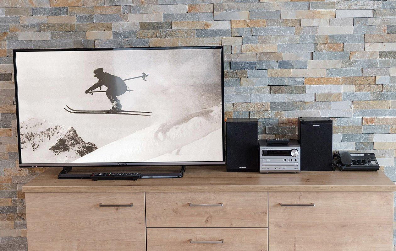 Flachbildfernseher und Stereoanlage auf einem Holzschrank