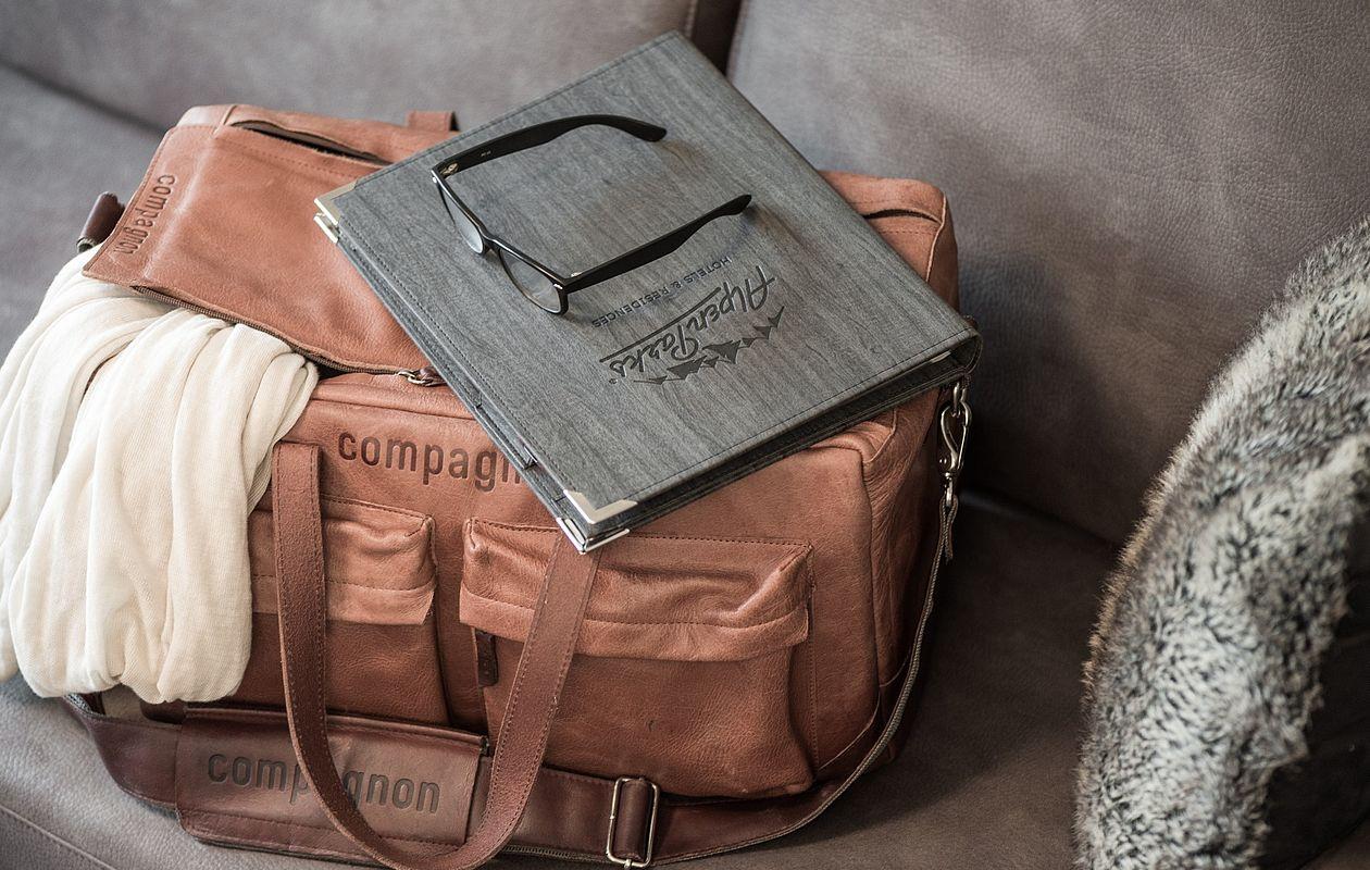 Gepackte Reisetasche mit Brille und Mappe darauf