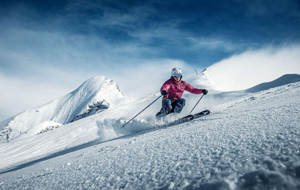 Junger Skifahrer genießt erste Abfahrt im Tiefschnee