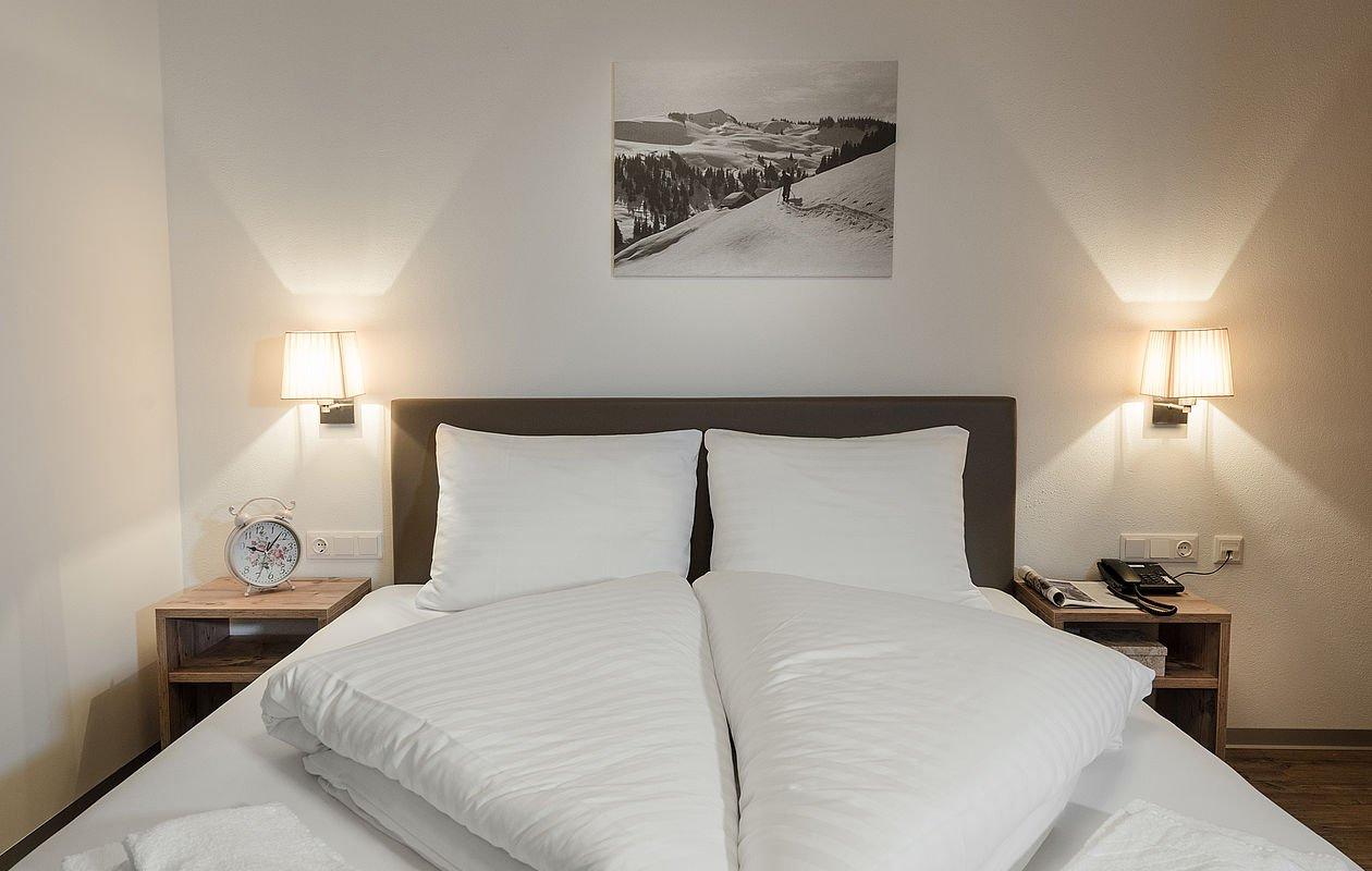 Schon gemachtes Doppelbett mit zwei Leuchten