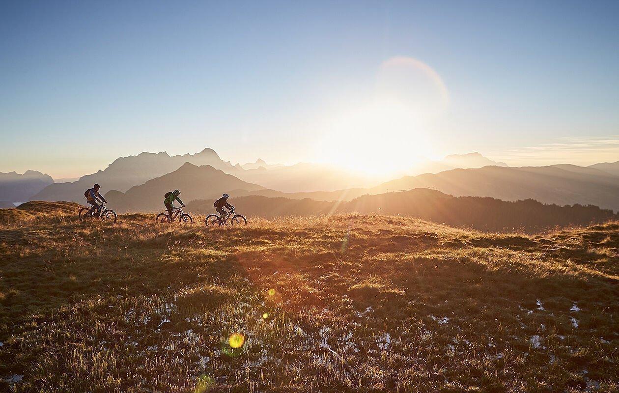 Gruppe von Mountainbikern genießen den Sonnenuntergang hoch in den Bergen