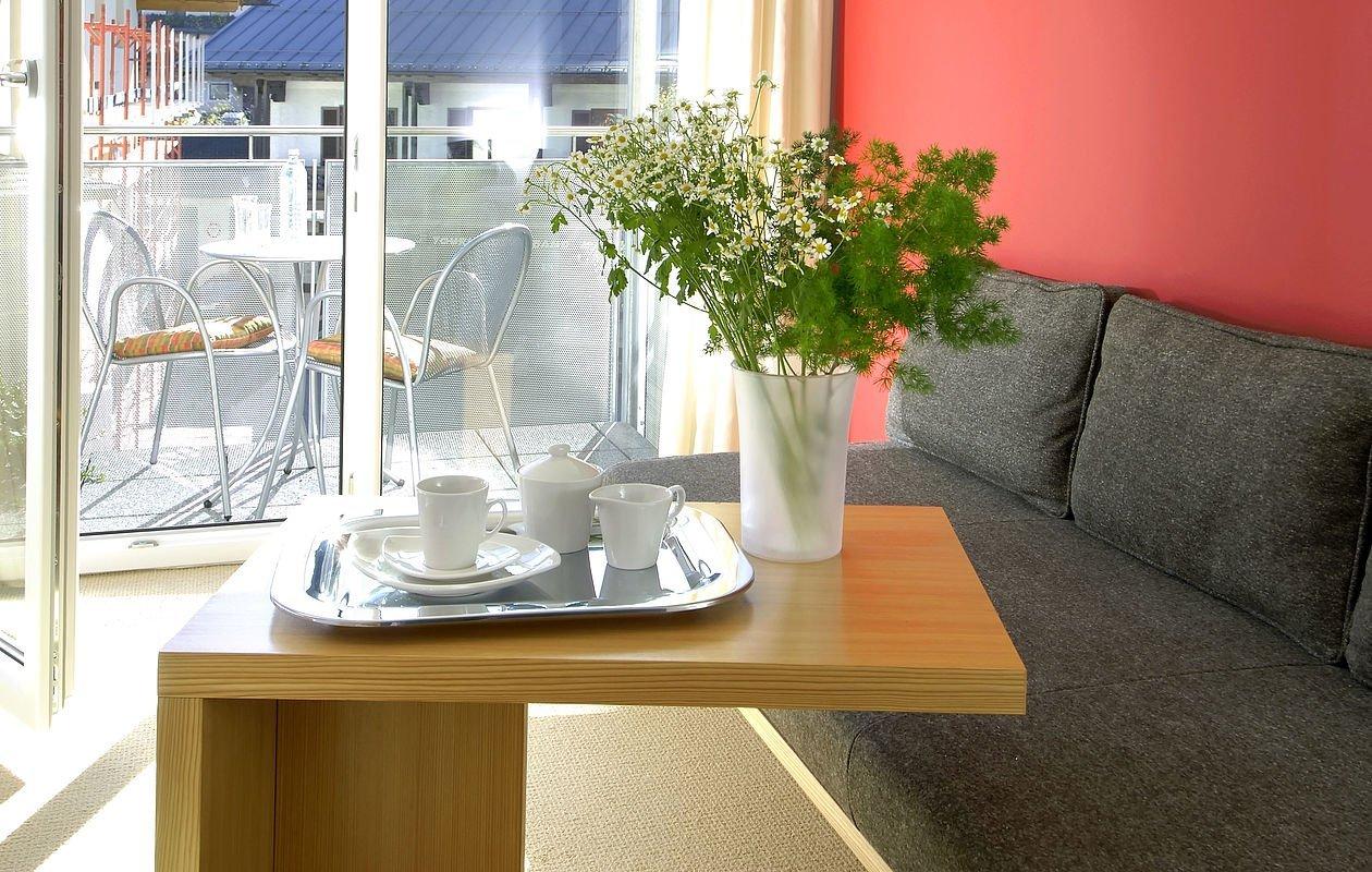 Couchtisch ist gedeckt mit Kaffeetassen und Blumen