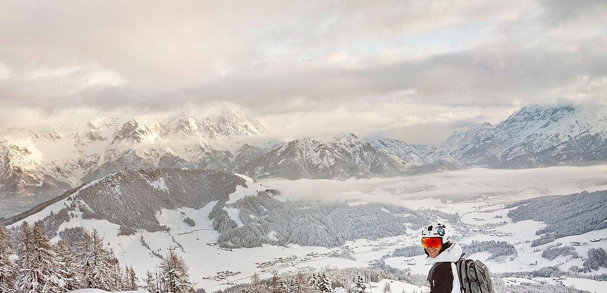Freerider steht in tiefverschneiter Landschaft in Saalbach