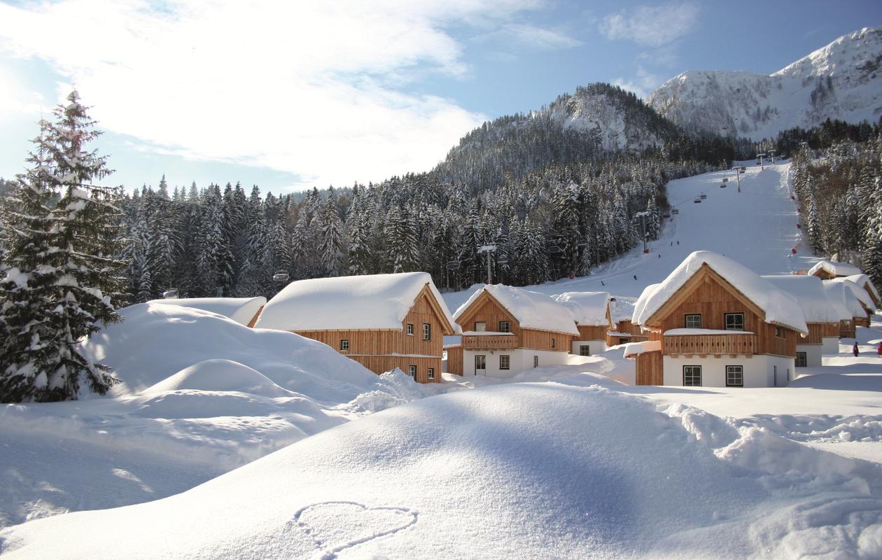 Tiefverschneite Landschaft mit Ferienhäusern und im Hintergrund sieht man die Skipisten vom Loser