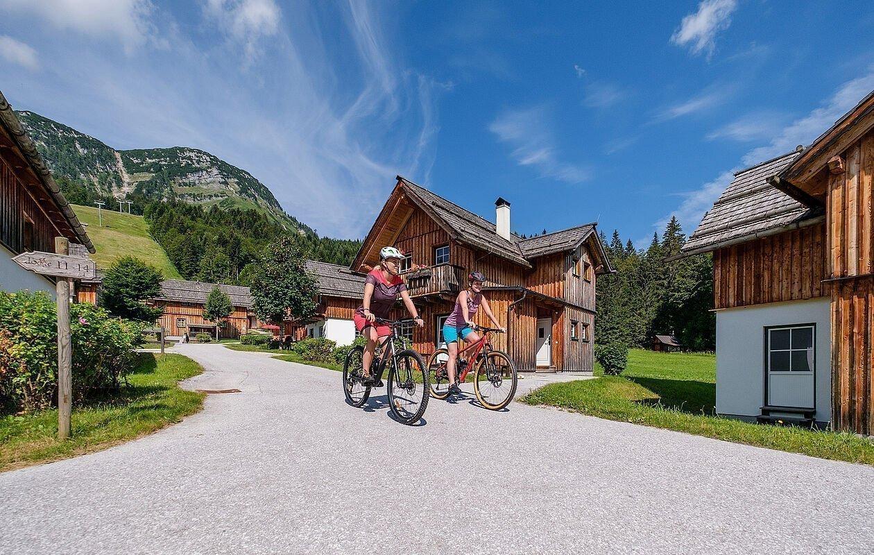Mountainbiker düsen durch das Hüttendorf der Hagan Lodge