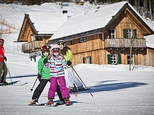Kinder fahren die Piste direkt vor den Chalets der Hagan Lodge in Altaussee runter