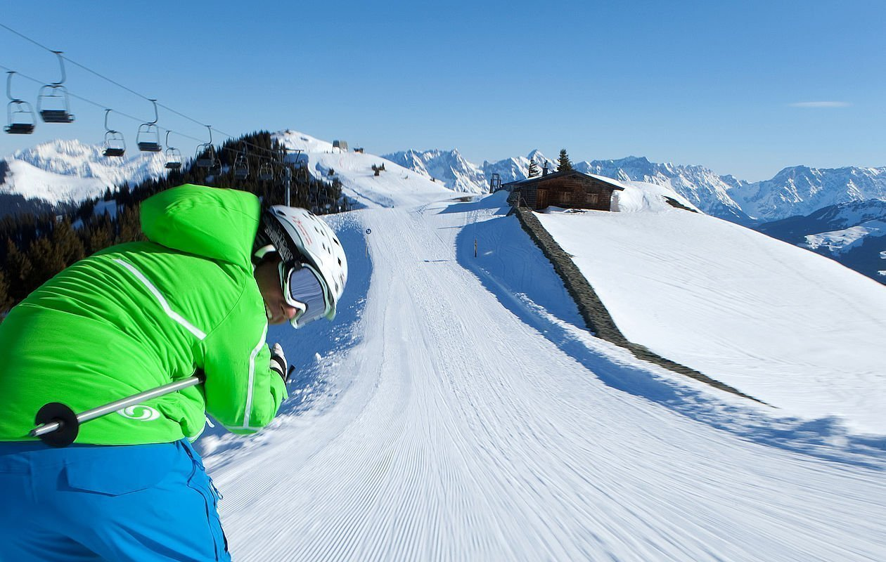Skifahrer düst mit Schwung die Piste entlang
