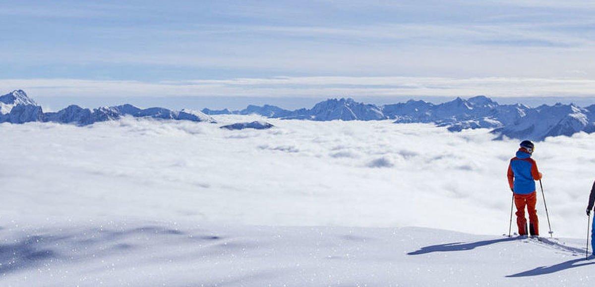 Skifahrer stehen in tiefverschneiter Landschaft über einem Wolkenmeer