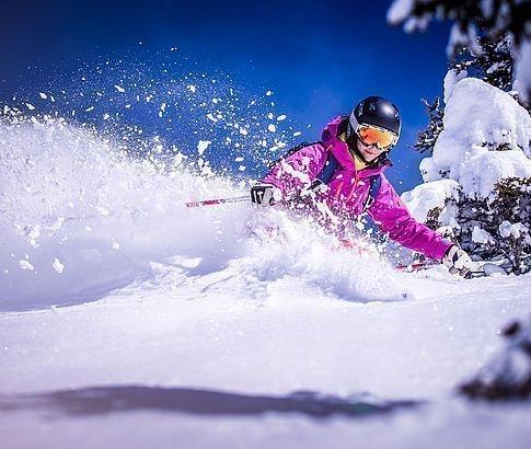 Skifahrer wedelt bei Neuschnee den Hang runter