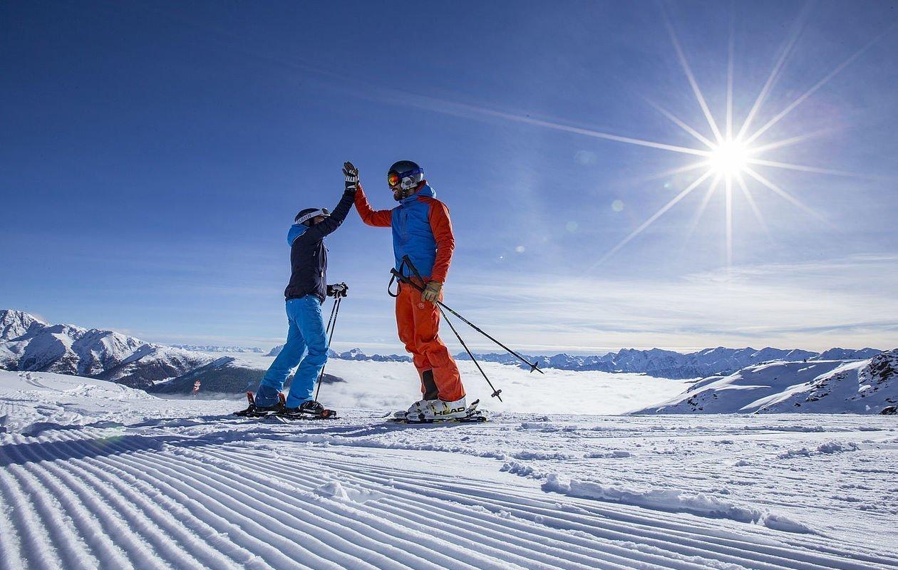 Skifahrer geben sich ein High-Five in den Bergen Osttirols