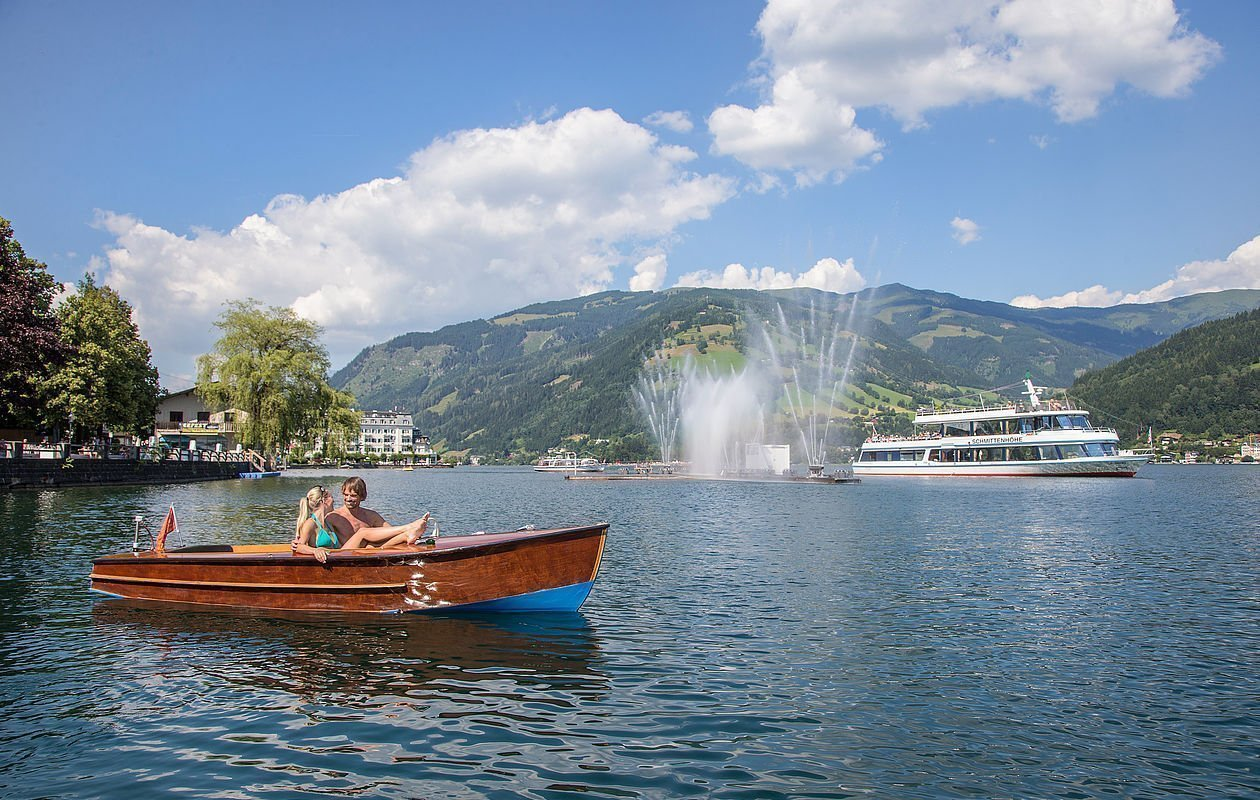 Boot mit Pärchen fährt am Zeller See entlang