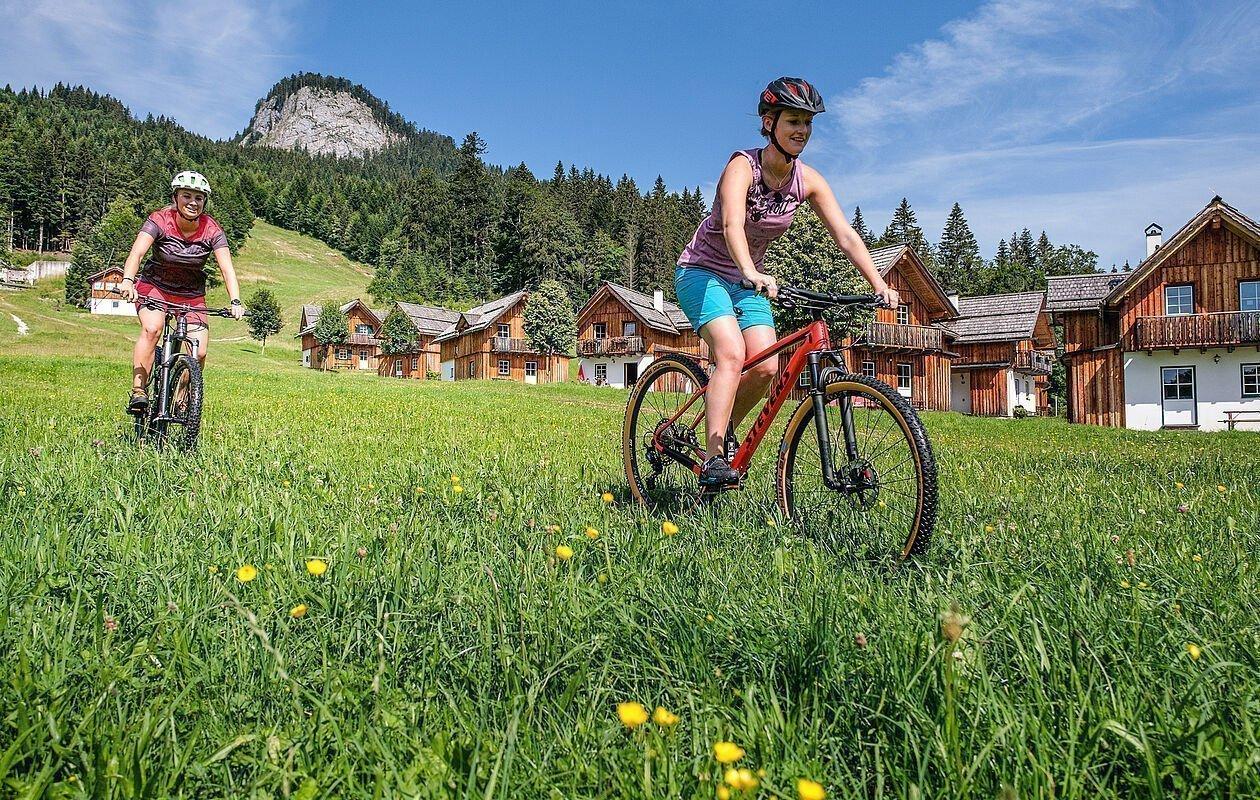 Mountainbiker auf einem Trail neben dem Hüttendorf