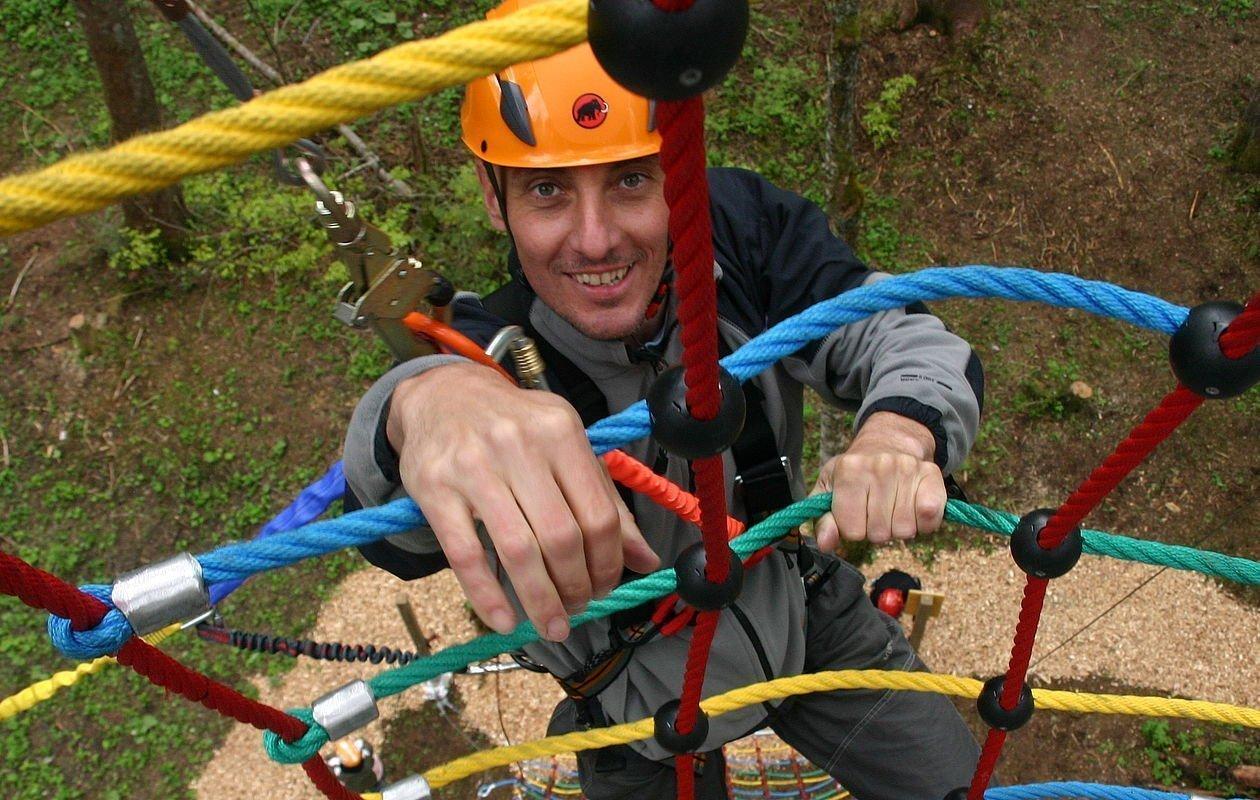Mann klettert im Hochseilpark