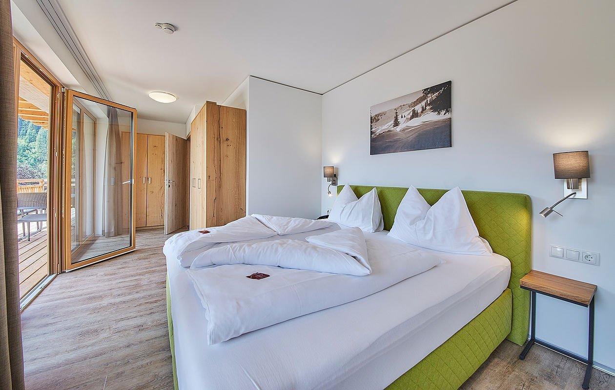 Sonnendurchflutetes Schlafzimmer mit Doppelbett, Kleiderschrank und Balkon